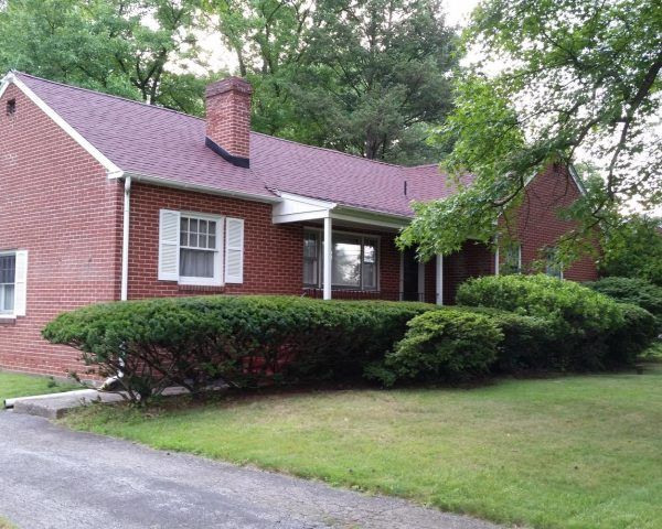 brick home with shingled roof and shrubberies