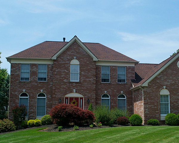 two story brick home with new roof materials