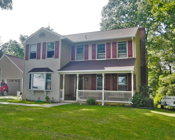 two story home with vinyl and brick siding and asphalt shingles