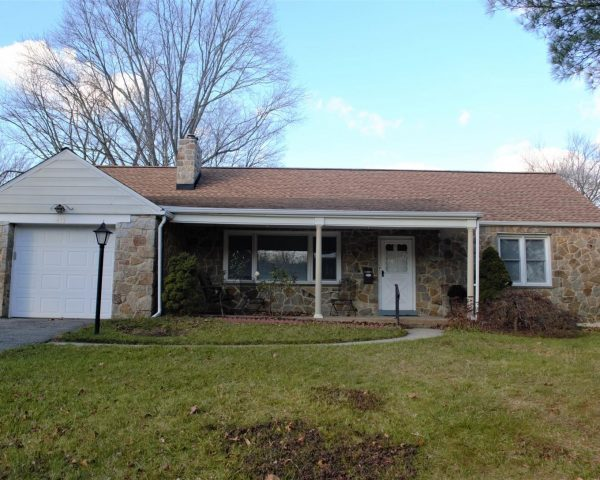 single story home with shingles and grass front lawn
