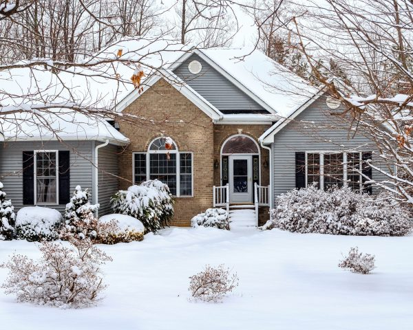 snow covered home with light blue siding