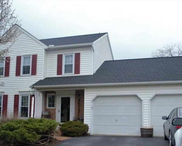 white home with asphalt shingles and two car garage