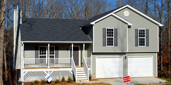 newly roofed delaware county home with white garage doors and vinyl siding