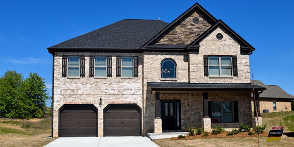 newly roofed home in delaware county with two garage doors and brick siding